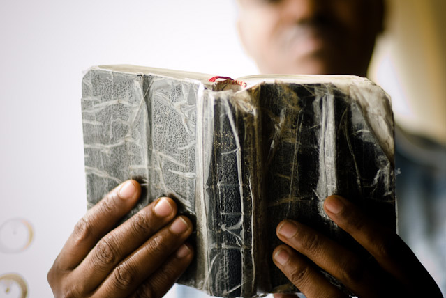 Eritrean refugees in Cardiff: Abraham with the bible he was given on reaching the UK. It's already very well thumbed.